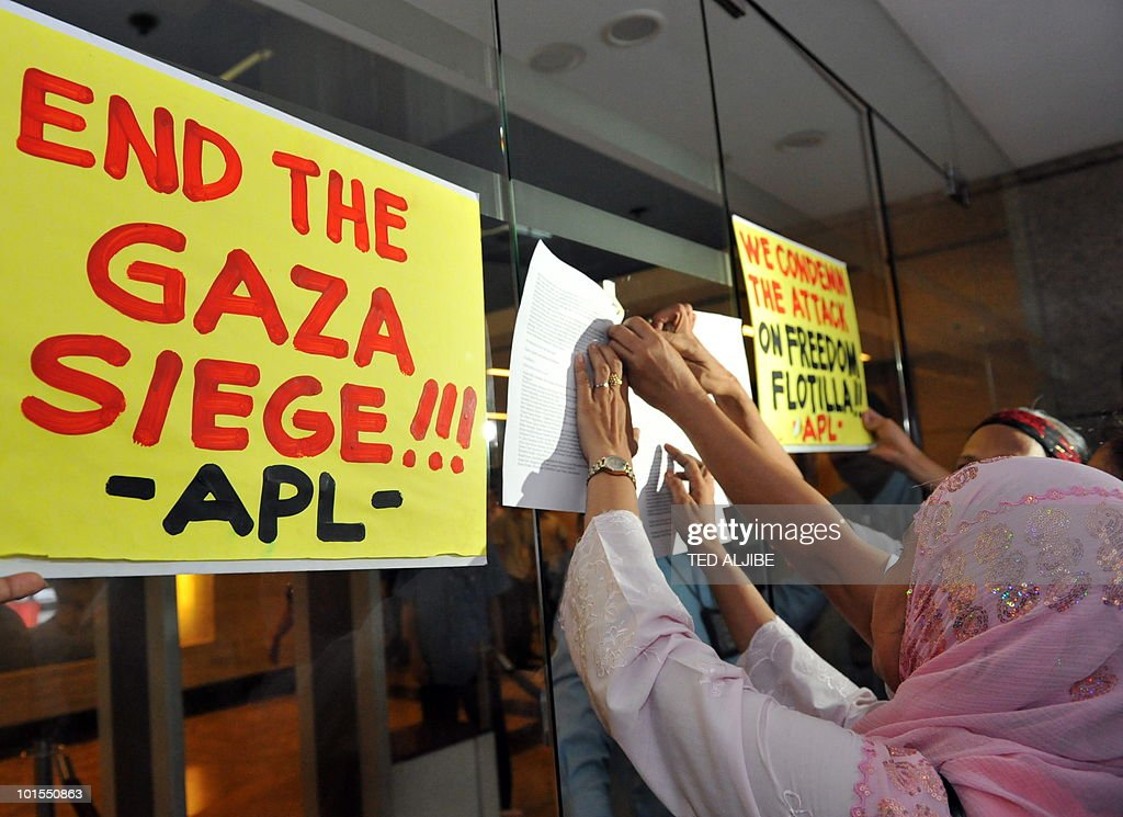 Protesters paste their letter to the Israeli ambassador on the glass door of the building housing Israeli embassy, after security officers refused to receive the letter, during a pro-Palestinian protest condemning the Israeli military action against the aid flotilla in the financial district of Manila on June 2, 2010. Activists in the Philippines on June 2, strongly condemned what they called a brutal attack by Israel on a Gaza-bound aid flotilla that left nine people dead.