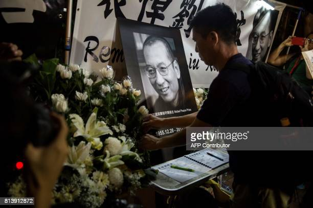 Protesters pay their respects outside the Chinese Liaison Office of Hong Kong after the death of Chinese Noble laureate Liu Xiaobo in Hong Kong on...