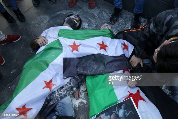 Protesters perform as victims with Syria's former independence flags as they simulate a chemical attack during a demonstration against chemical...