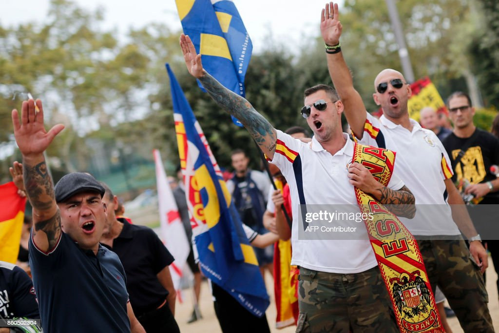 Protesters perform the fascist salute during an ultra-right wing anti-separatist demonstration for the unity of Spain called by 'Falange Espanola' during the Spanish National Day (Dia de la Hispanidad) in Barcelona on October 12, 2017. Spain marks its national day today with a show of unity in the face of Catalan independence efforts, a day after the central government gave the region's separatist leader a deadline to abandon his secession bid. The country is suffering its worst political crisis in a generation after separatists in the wealthy northeastern region voted in a banned referendum on October 1 to split from Spain BARRENA