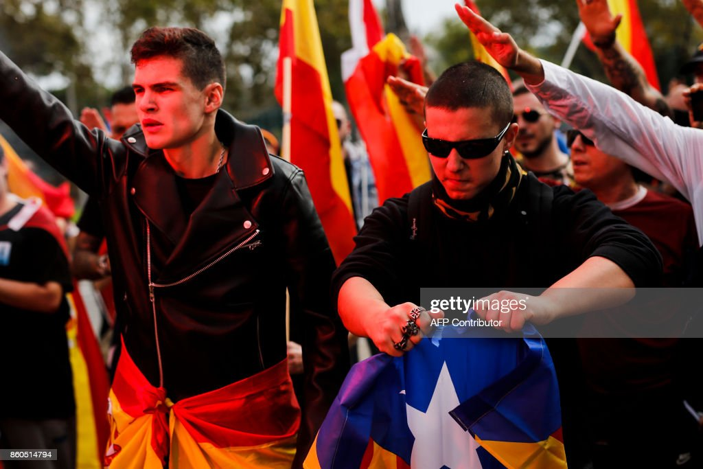 Protesters perform the fascist salute while a man tears an 'Estelada' Catalan pro-independence flag during an ultra-right wing anti-separatist demonstration for the unity of Spain called by 'Falange Espanola' during the Spanish National Day (Dia de la Hispanidad) in Barcelona on October 12, 2017. Spain marks its national day today with a show of unity in the face of Catalan independence efforts, a day after the central government gave the region's separatist leader a deadline to abandon his secession bid. The country is suffering its worst political crisis in a generation after separatists in the wealthy northeastern region voted in a banned referendum on October 1 to split from Spain BARRENA