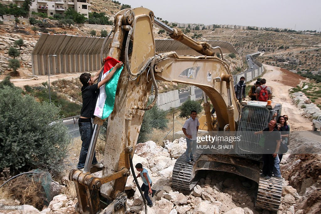 Protesters place a Palestinian flag on a bulldozer at the construction site of Israel's controversial separation barrier in the West Bank town of...