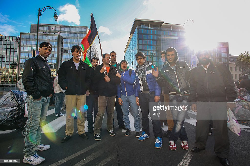 Protesters pose during a demonstration of Afghan refugees on the Wetstraat - rue de la Loi in Brussels on October 29, 2013.