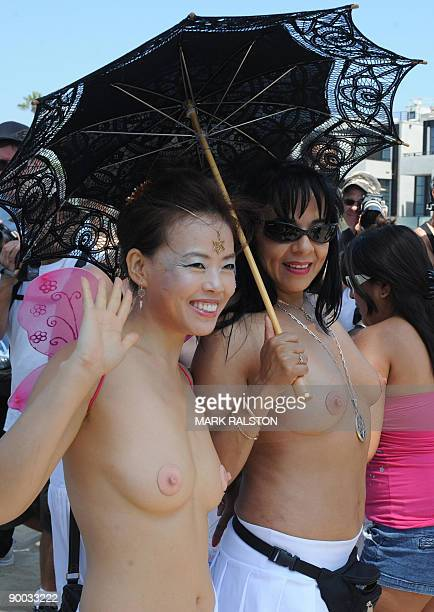 Protesters pose for photos as they prepare to march during 'National Go Topless Day' to honor Women's Equality Day at Venice Beach in Los Angeles on...