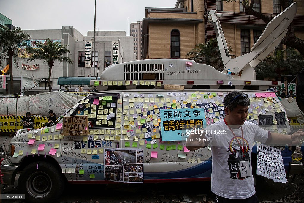 Protesters post anti-media slogans on a van which belongs to a TV station known for being pro-government, during rally outside the legislature on March 24, 2014 in Taipei, Taiwan. Clashes erupted between protesters and police after Taiwan's president refused to scrap a contentious trade agreement with China and denounced the 'illegal' occupation of parliament by students opposed to its ratification.
