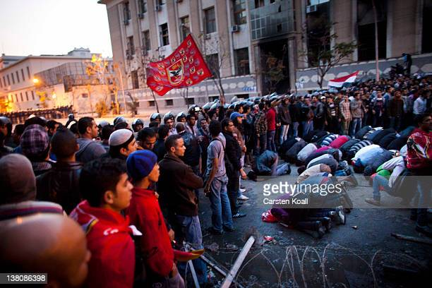 Protesters pray as they are blocked by police on their way to the interior ministry after a demonstration outside Cairo's Al Ahly football stadium on...