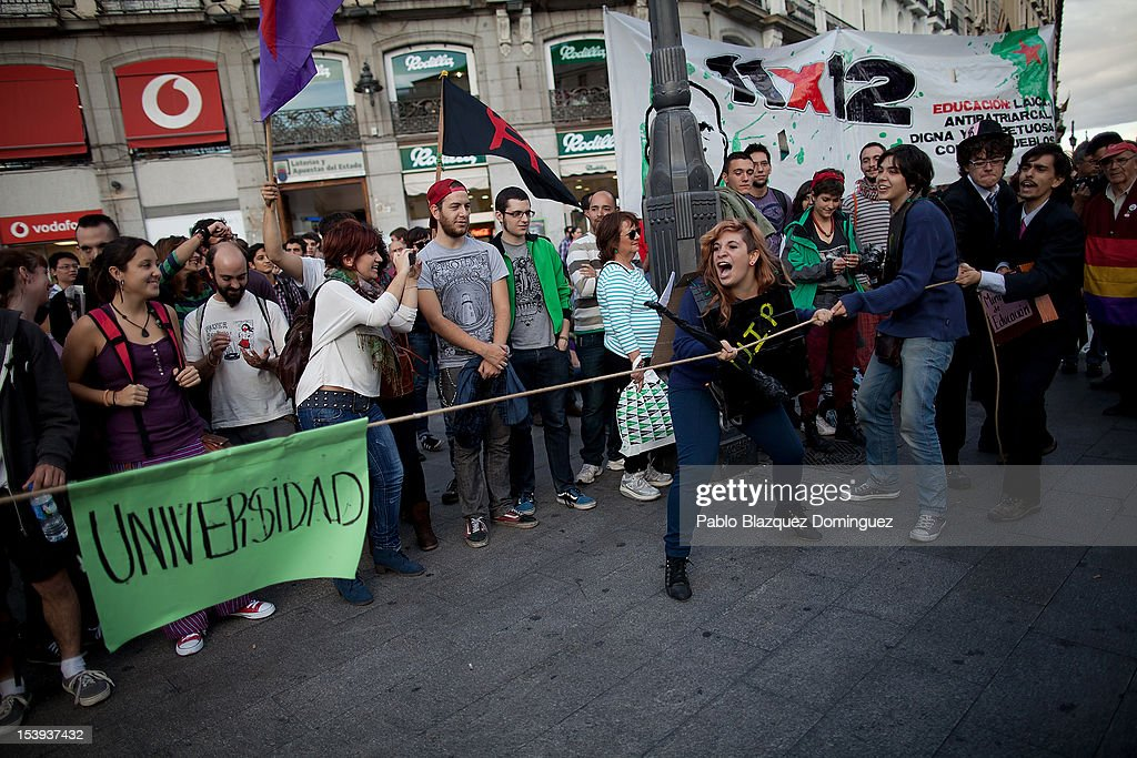Protesters pull on a rope during a performance at a demonstration by students protesting against education cuts at Puerta del Sol on October 11, 2012 in Madrid, Spain. Ratings agency Standard & Poor's has cut Spain's credit rating down to BBB-. The Spanish government has already introduced spending cuts and tax increses in an attempt to ease the country's debt and reduce high unemployment levels. Spain's Minister of Economy Minister Luis de Guindos maintains that the country will not need to request a bailout.