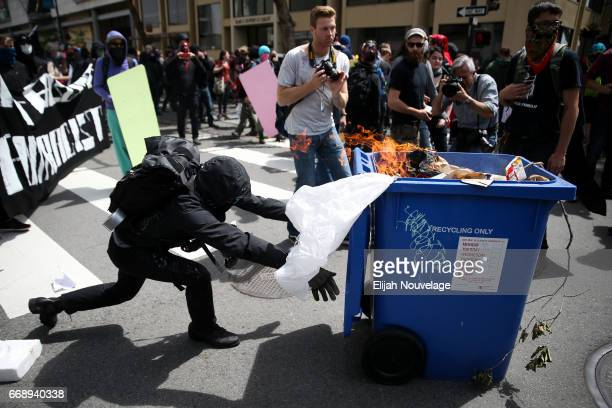 Protesters push a burning recycling bin at Trump supporters during a 'Patriots Day' free speech rally on April 15 2017 in Berkeley California More...