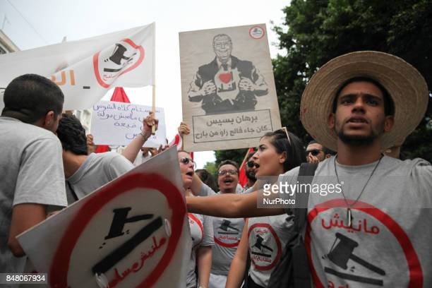 Protesters raise a portrait of Borhane Bsais leader in Nidaa Tounes ruling party that reads ' I Love corruption' during a march held under the slogan...