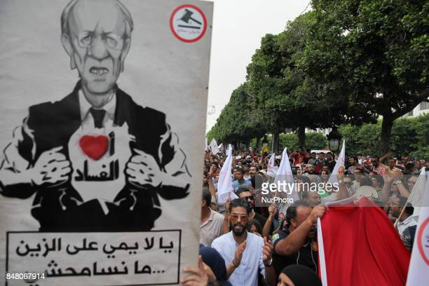Protesters raise a portrait of Tunisian president Beji Caid Essebsi that reads ' I Love corruption' during a march held under the slogan firmness...