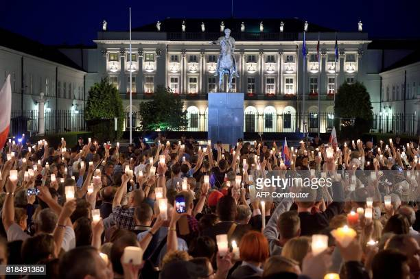 Protesters raise candles during a protest on July 18 2017 in front of the presidential palace in Warsaw as they urge the Polish President to reject a...