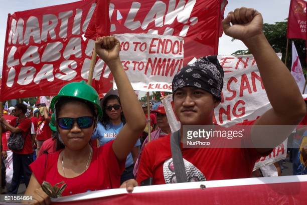 Protesters raise clenched fists during a rally coinciding President Rodrigo Duterte's annual State of the Nation Address in Quezon City northeast of...