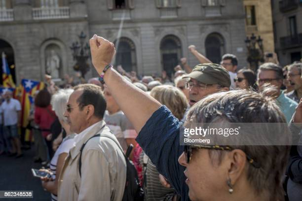 Protesters raise their fists during a silent demonstration outside the Generalitat in support of arrested Catalan independence campaigners Jordi...