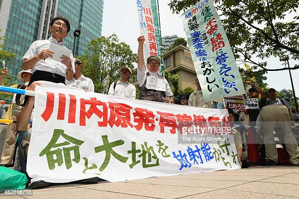 Protesters rally outside a building that houses the office of the Nuclear Regulation Authority which is screening the safety of the Kyushu Electric...