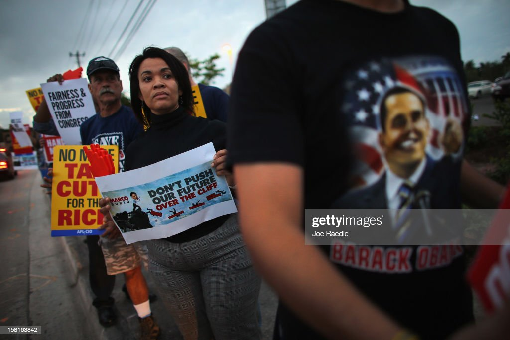 Protesters rally together outside the office of U.S. Sen. Marco Rubio (R-FL) on December 10, 2012 in Doral, Florida. The protesters are hoping that Senators like Rubio will not cut medicare/social security benefits and will agree to raise taxes on the top 2% of earners in the country.