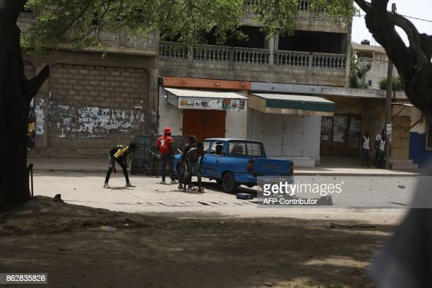 Protesters react in a street where opposition supporters have erected makeshift barricades and block roads in Lome on October 18 2017 Protesters...