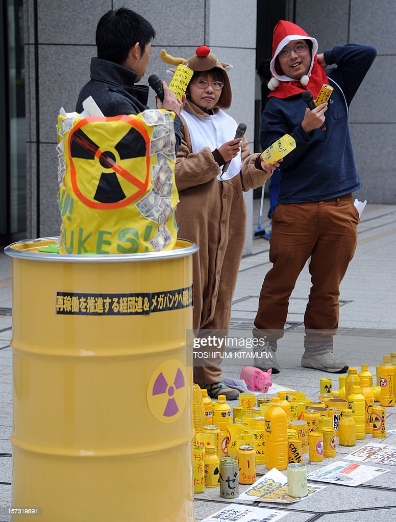 Protesters read messages as they stage an anti-nuclear power plant demonstration outside the Keidanren (Japan Business Federation) headquarters in central Tokyo on December 2, 2012. Protesters were demanding that Japan's economic leaders not support the re-starting of the country's nuclear power plants. AFP PHOTO / TOSHIFUMI KITAMURA
