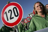 Protesters representing the German Traffic Club hold up road signs indicating a speed limit of 120km per hour outside the Chancellery March 27 2007...