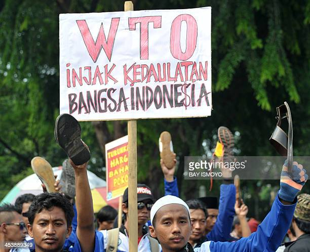 Protesters rise their shoes in the air during ananti WTO rally in front of US embassy in Jakarta on December 6 2013 World commerce ministers engaged...