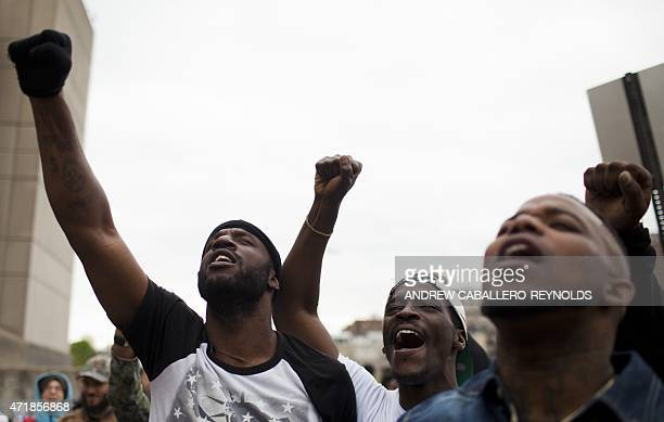 Protesters rise up their fists outside the Baltimore Police Central Booking and Intake Center for prisoners in Baltimore Maryland on May 1 2015 Six...
