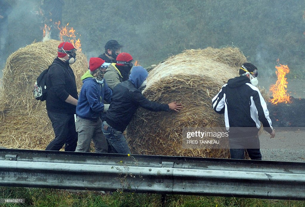 Protesters roll a bundle of hay on October 26, 2013 in Pont-de-Buis, western France, as they demonstrate against an ecotax that will come into effect on January 1, 2014. Demonstrators protesting at the last ecotax control portal still standing in the French western department of Finistere threw projectiles at police, who answered with tear gas. AFP PHOTO/FRED TANNEAU