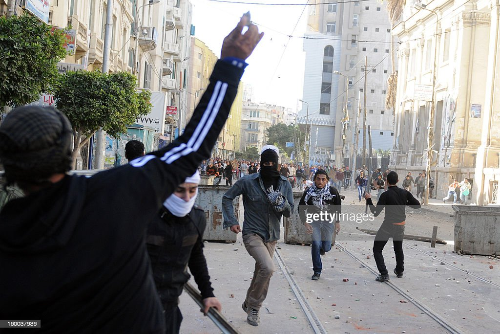 Protesters run away during a rallye marking the second anniversary of the uprising that ousted Hosni Mubarak and ushered in an Islamist government on January 25, 2013 in Alexandria. Clashes erupted in two neighbourhoods of Alexandria between police and protesters who burned tyres, sending plumes of dark smoke into the sky.