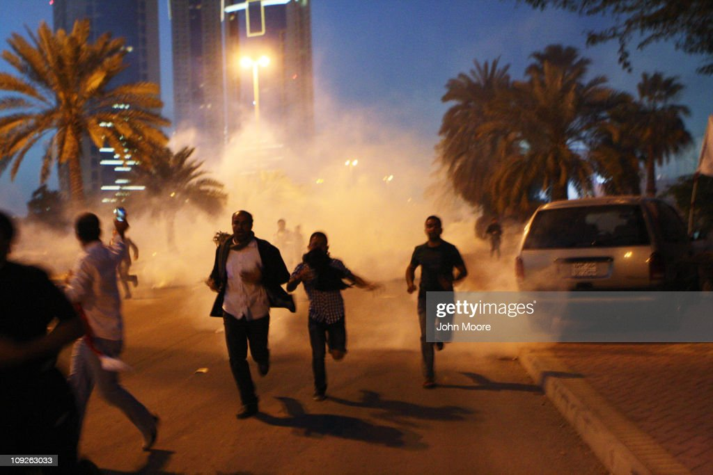 Protesters run from a cloud of teargas during a clash with Bahraini security forces near the Pearl roundabout on February 18 2011 in Manama Bahrain...
