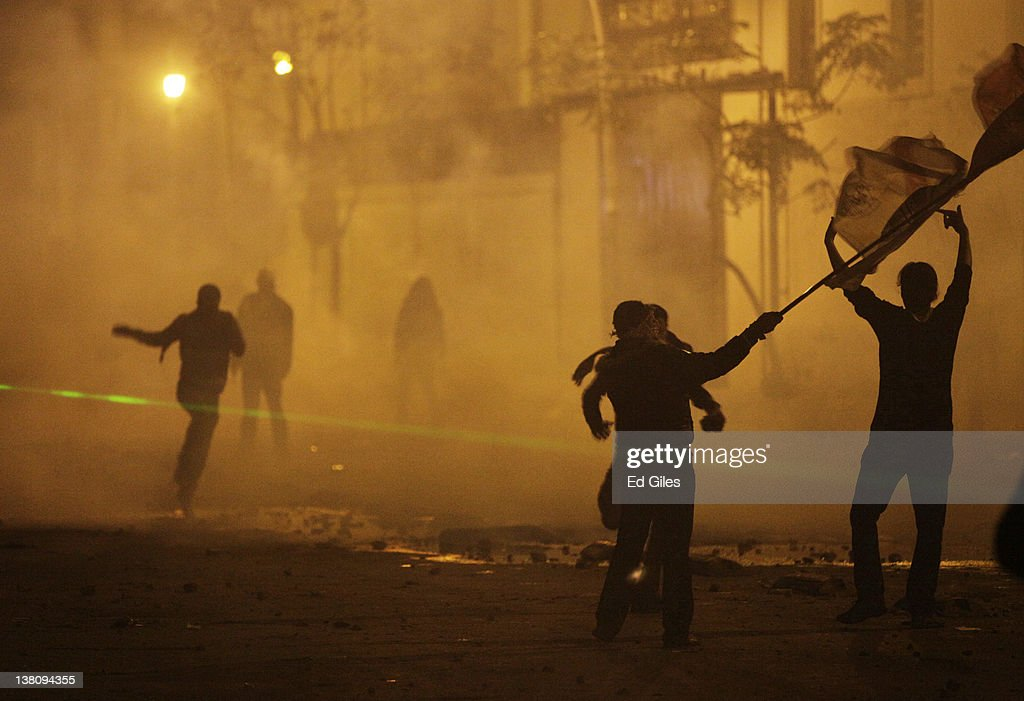 Protesters run through clouds tear gas fired by security forces February 2 2012 in Cairo Egypt The protest follows the deaths of 74 football fans...