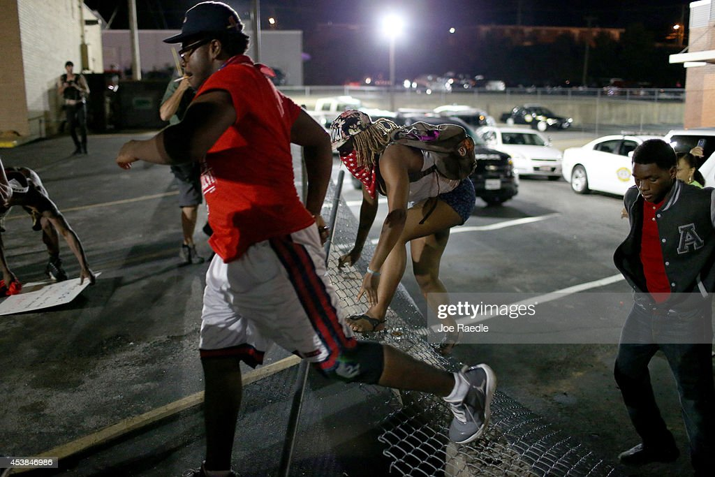 Protesters scramble as they try to evade police who ran into the crow to make an arrest on August 19, 2014 in Ferguson, Missouri. Violent outbreaks have taken place in Ferguson since the shooting death of unarmed teenager Michael Brown by a Ferguson police officer on August 9th.