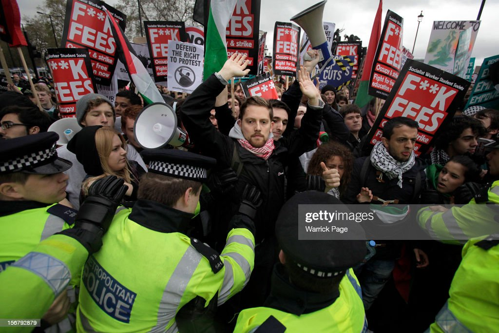 Protesters scuffle with police and shout slogans during a demonstration against education cuts, tuition increases and austerity outside the Houses of Parliament on November 21, 2012 in London, England. The demonstration march was organised by the National Union of Students and is the first national student protest since a series of violent protests against tuition fees two years ago.