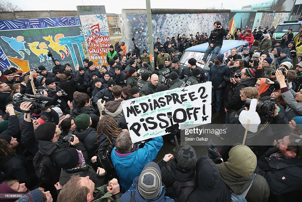 Protesters scuffle with police at the East Side Gallery, which is the longest still-standing portion of the former Berlin Wall, during efforts by a construction company to remove a 25-meter long section of the Wall on March 01, 2013 in Berlin, Germany. A real estate developer is planning to build a 14-storey apartment building between the Wall and the Spree River, and needs to remove the Wall section in order to allow access to the construction site. Critics, including East Side Gallery mural artists and Spree River embankment development opponents, decry the move, citing the importance of the East Side Gallery's status as a protected landmark and a major tourist attraction. The East Side Gallery is approximately 1.3 kilometers long.
