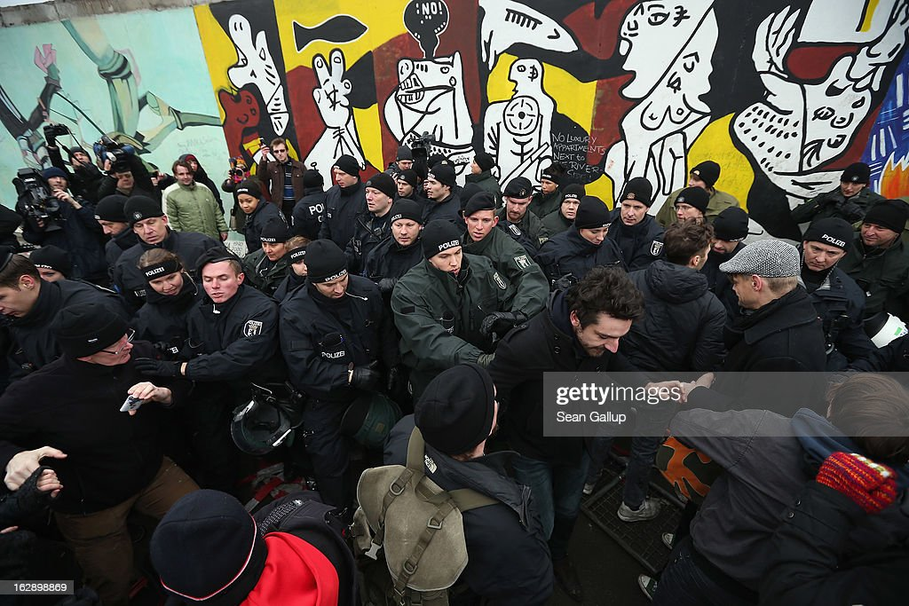 Protesters scuffle with police at the East Side Gallery, which is the longest still-standing portion of the former Berlin Wall, following efforts by a construction company to remove a 25-meter long section of the Wall on March 1, 2013 in Berlin, Germany. A real estate developer is planning to build a 14-storey apartment building between the East Side Gallery and the Spree River, and needs to remove the Wall section in order to allow access to the construction site. Critics, including East Side Gallery mural artists and Spree River embankment development opponents, decry the move, citing the importance of the East Side Gallery's status as a protected landmark and a major tourist attraction. The East Side Gallery is approximately 1.3 kilometers long.