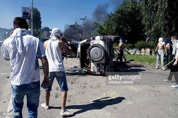 Protesters set fire to a car during clashes with Kosovo riotpolice on June 22 2014 in the divided town of Mitrovica Kosovo police used tear gas today...