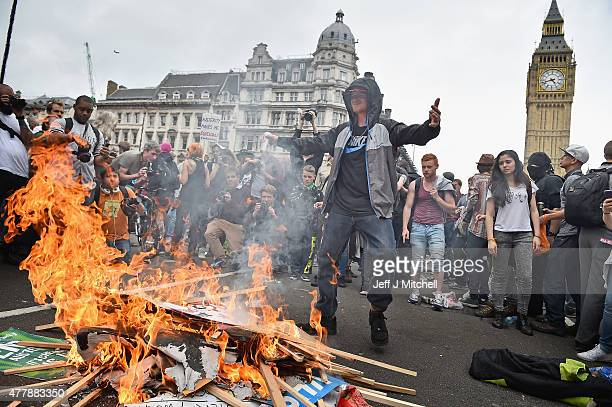 Protesters set fire to placards in central London during a demonstration against austerity and spending cuts on June 20 2015 in London England...