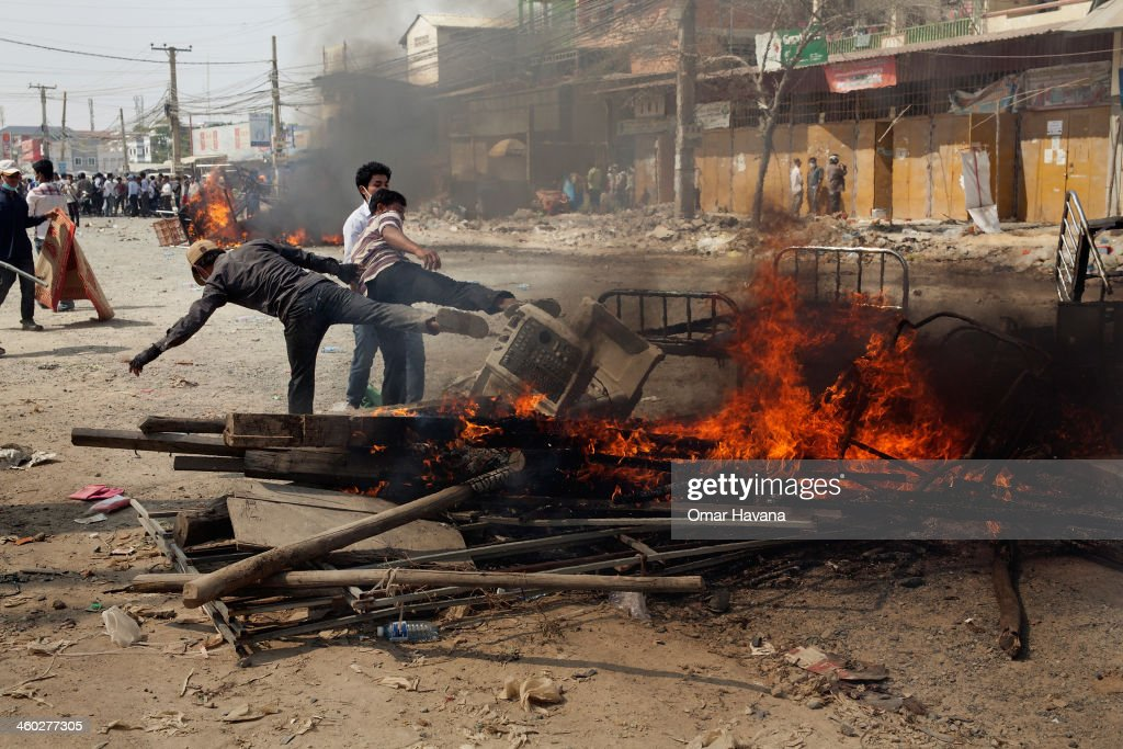 Protesters set up a burning barricade during demonstrations held by garment workers on January 3, 2014 in Phnom Penh, Cambodia. Several people have been injured, and at least three people have reported dead after police broke up demonstrations on Veng Sreng Boulevard by garment workers demanding wage increases beyond the industry minimum wage set last week by the Ministry of Labour's Labour Committee.