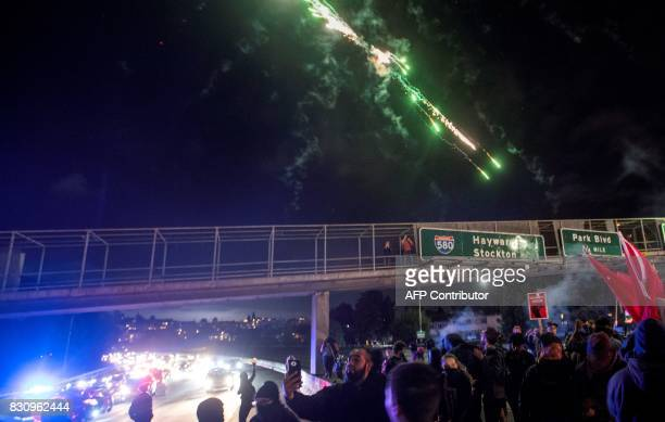 Protesters shoot fireworks into the air as they block the Interstate 580 freeway in both directions to rally against racism in Oakland California on...