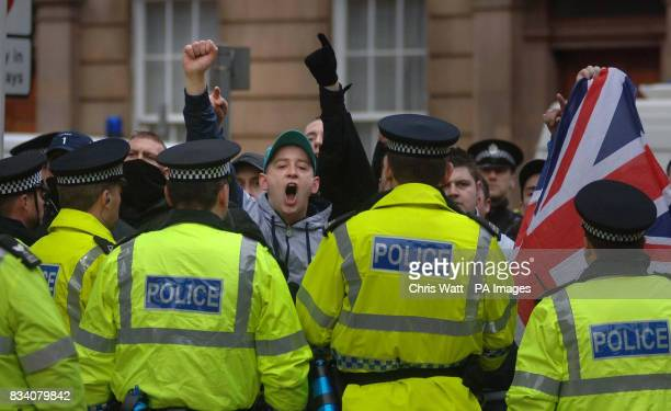 Protesters shout and gesture behind rows of police officers at a parade to remember the victims of Bloody Sunday in Glasgow this morning