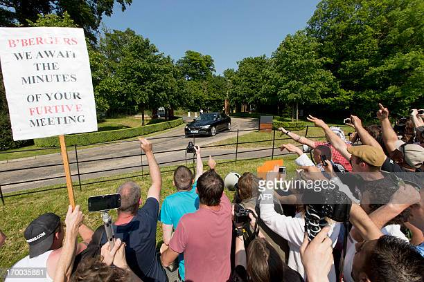 "Protesters shout and wave a placard that reads 'B'Bergers we await the minutes of your furtive meeting"" as a vehicle arrives at the drive to the..."