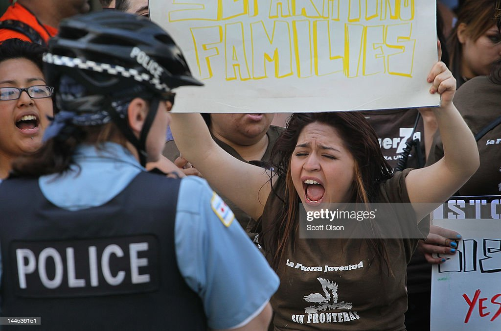 Protesters shout as Chicago police guard the building which houses immigration court on May 15, 2012 in Chicago, Illinois. At least four people were arrested at the protest where demonstrators were calling for immigration reform. This was the second day of protests in what is expected to be a full week of demonstrations as the city prepares to host the NATO Summit May 20-21.
