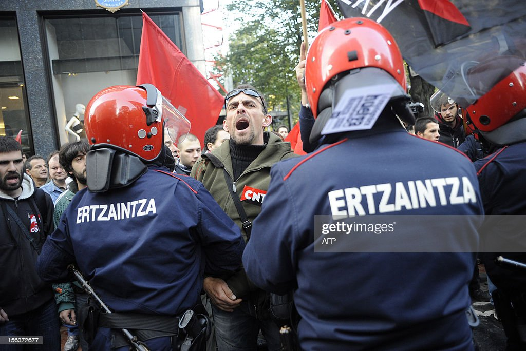 Protesters shout in front of Basques riot policemen during a picketing in front of a shopping center on November 14, 2012 in Bilbao during a general strike. General strikes in Spain and Portugal will spearhead the day of action called by European unions and joined by activists as anger over governments' tight-fisted policies boils over.