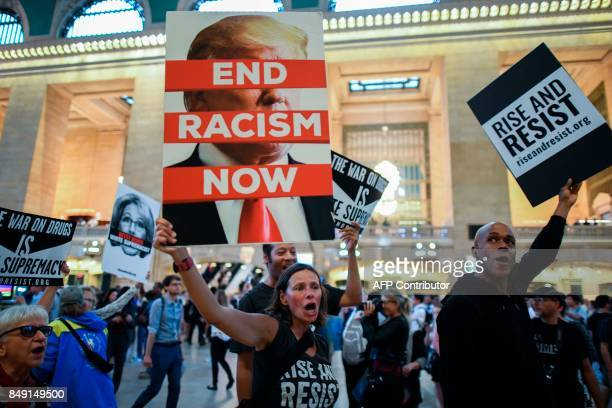 TOPSHOT Protesters shout slogans and wave placards against US President Donald Trump during Rise and Resist Against White Supremacy demonstration...