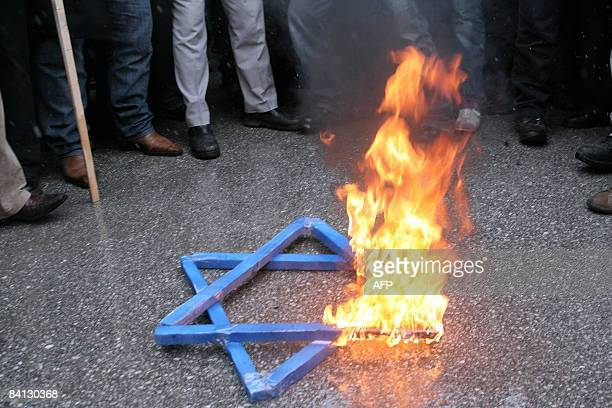 Protesters shout slogans as a Star of David burns at a protest against Israeli attacks on Gaza in front of Israel's Embassy in Ankara on December 28...