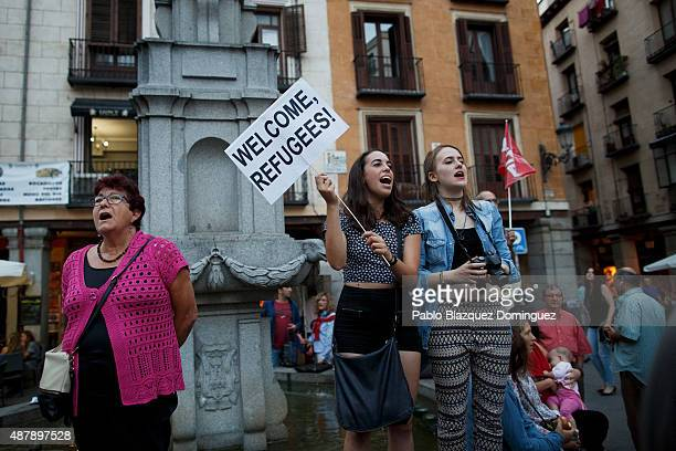 Protesters shout slogans as one holds a placard reading 'Welcome refugees' during a demonstration to show solidarity and support for refugees on...