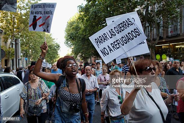 Protesters shout slogans as they hold placards reading 'No wars no walls' and 'Stop wars not refugees' during a demonstration to show solidarity and...