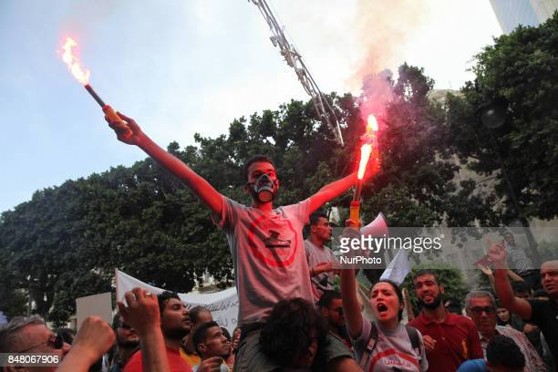 Protesters shout slogans as they hold smoke grenades during a march held under the slogan firmness against the mafia regime by the movement quotI...