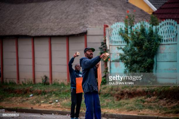 Protesters shout slogans during clashes with South African riot police in the Eldorado Park district in Johannesburg on May 8 2017 following a...