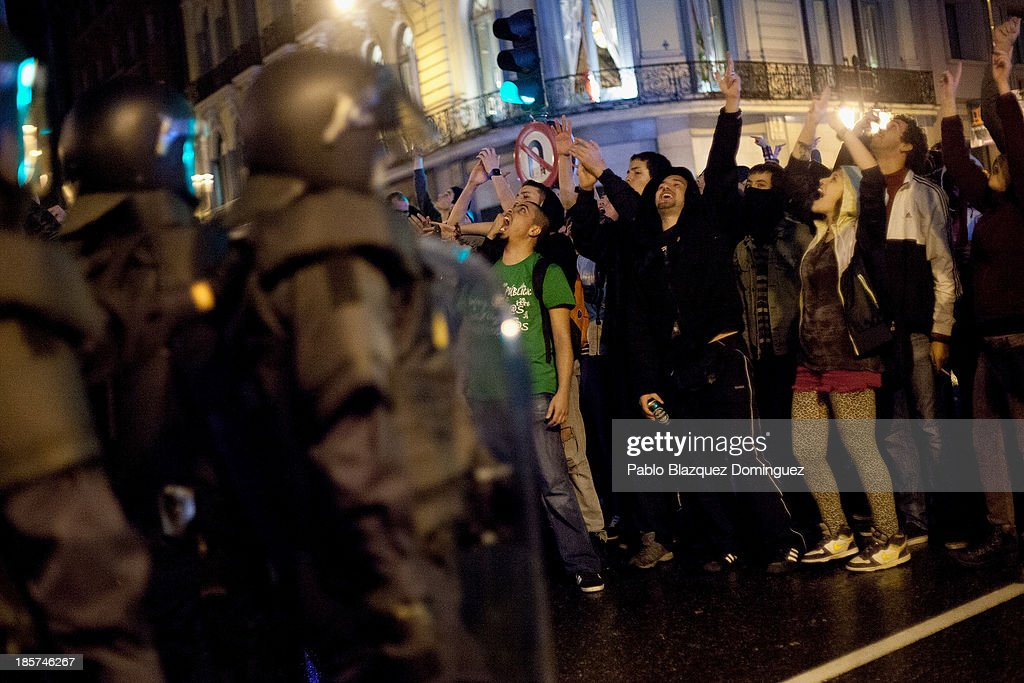 Protesters shout slogans next to riot police after a demonstration at Alcala Street on October 24, 2013 in Madrid, Spain. The Spanish Parliament recently approved a controversial reform of the educational system, which passed by the ruling right wing People's Party (PP) using their absolute majority and not backed by any other political party. The students are on a three day strike to protest against the new law, which will need to be approved by the senate next month and are calling for the resignation of Education Minister, Jose Ignacio Wert.