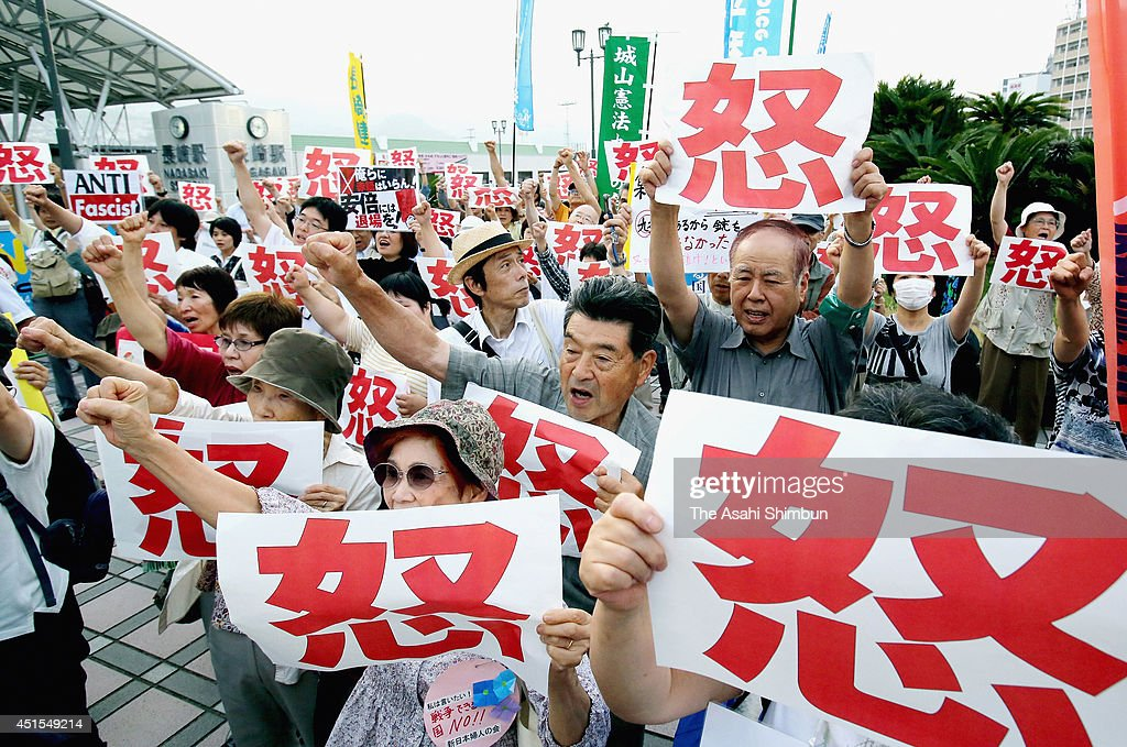 Protesters shout their opposition to the Abe Cabinet's move to allow Japan to exercise the right to collective self-defense with holding banners of the 'Anger' on July 1, 2014 in Nagasaki, Japan. Prime Minister Shinzo Abe's Cabinet approved changes to Japan's postwar security policy that could lead to the Self-Defense Forces' use of military force in overseas battles. The Cabinet approved a document that revises the government's interpretation of war-renouncing Article 9 of the Constitution to allow Japan to exercise the right to collective self-defense.