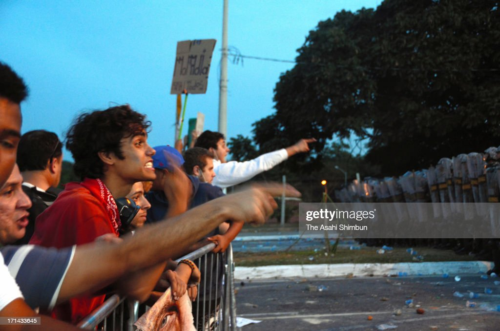 Protesters shout toward police officers standing guard at one kilometers check point from Estadio Mineirao, on June 22, 2013 in Belo Horizonte, Brazil. 60,000 protesters gather and 12 injured.