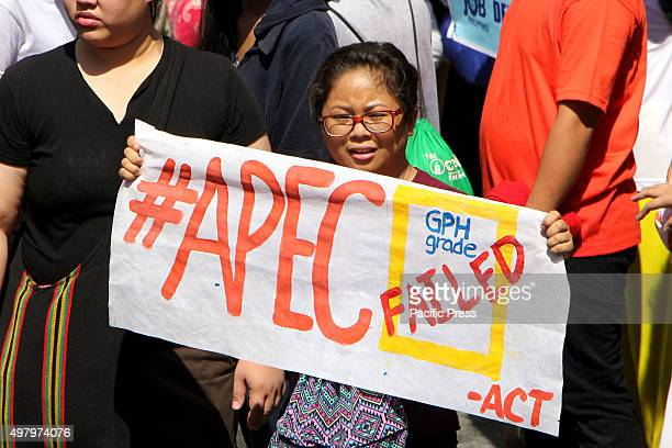 Protesters showing her grading about the APEC summit during their protest march in Buendia Avenue in Pasay City the militant group trying to get...